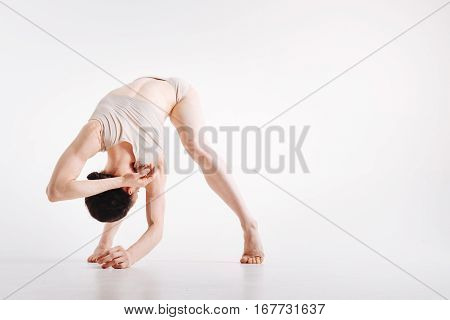 Enjoying stretching of my body. Flexible young masterful woman demonstrating her flexibility and expressing grace while practicing yoga in the white colored studio