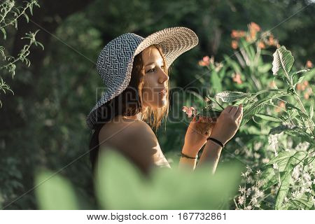 Beautiful girl standing in the forest wearing a straw hat, topless park, conceptual idea, a beautiful figure, smelling the flowers on summer vacation. Tanned skin. Life style