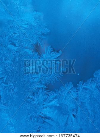 Slightly blurred beautiful frost pattern on a window glass with copyspace for your text (as an abstract winter background)