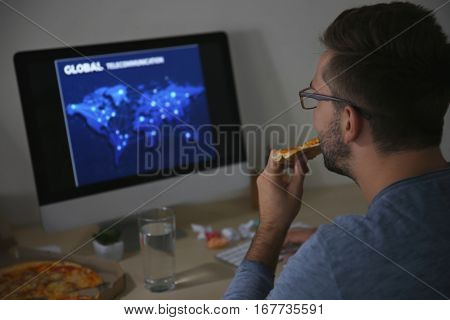 Man eating pizza while working with computer late in evening, close up view