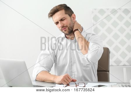 Handsome man suffering from neck pain in office