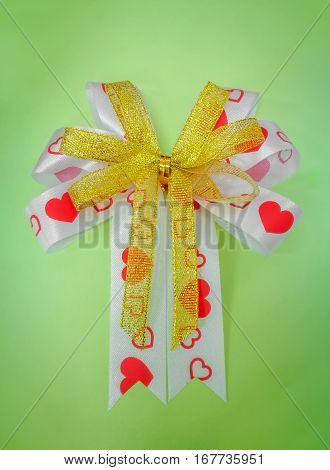 white and gold ribbon bow with red heart shape on green background