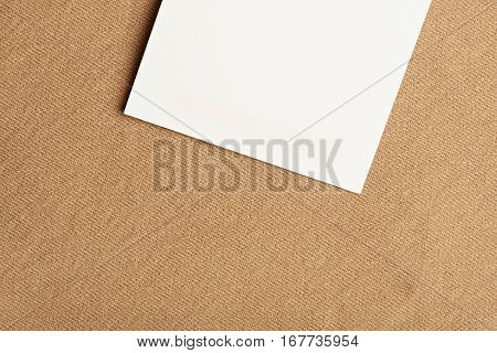White paper tag on yellow brown cloth fabric textile background