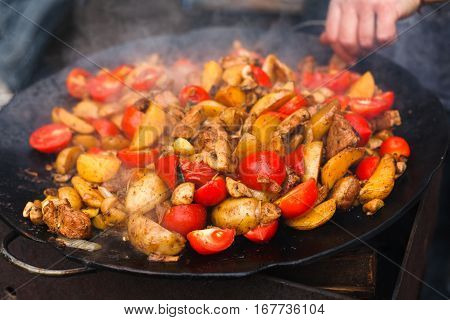Country fair, vendor cooking. Roasted potatoes with tomatoes, meat and mushroomes cooked outdoors in big metal cauldron pot. Cookout meals. Fresh snack on grill flame. Street fast food.
