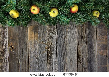 organic tiny apples in Christmas pine garland on rustic wood
