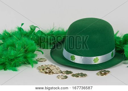 Green felt hat with feather boa and gold coins for St. Patrick's Day background