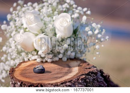Wedding and engagement ring with black silicone mans ring on wooden stump with white roses in background