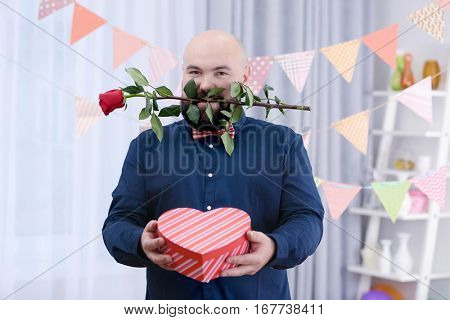 Funny fat man with giftbox and flower at birthday party