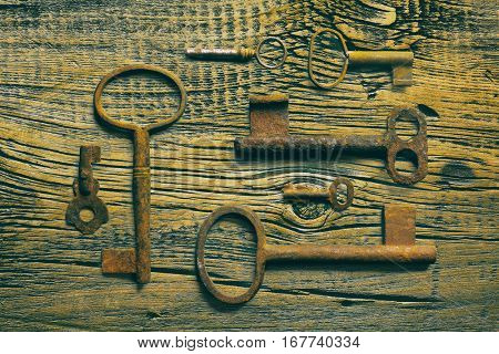 rusty medieval keys on worn out wood table. Antique and rusty medieval castle skeleton door keys with old corroded metal ring on antique weathered barn wood board planks