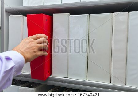 Man's hand taking off the shelf red folder with documents archive file stock photo