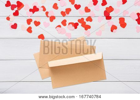 Valentine day letter. Envelope from craft paper with red heart on it, on white wood background. Lover's holiday confession or proposal concept