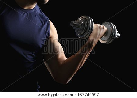 Sporty man doing exercises with dumbbell on black background, closeup