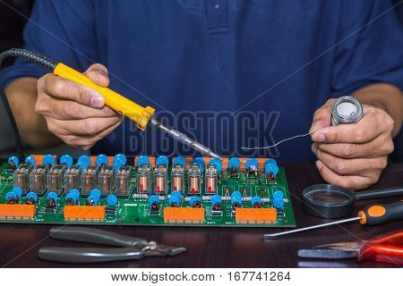 Technician holds soldering iron and solder to do board repairing
