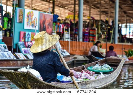Bangkok / Thailand - January 20 2017: Old woman working with a boat in the floating market nearby to Bangkok