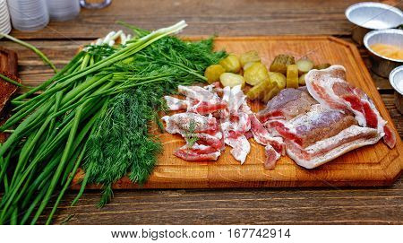 Salted pork lard salo with onion and dill c on a wooden board. Rustic style