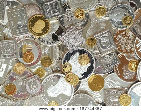 coins medals ans stamps of pure silver and gold background