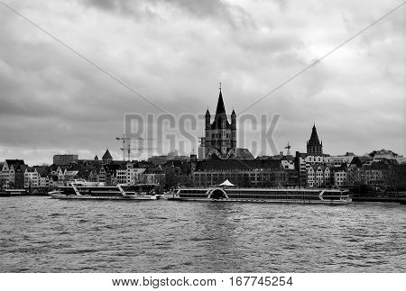 View on Great Saint Martin Church and left bank of the Rhine in cloudy weather Cologne Germany. Black and white panorama of the city