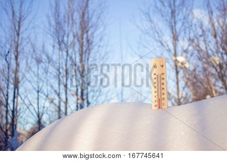 Thermometer in snow the picture was taken from below on a blue sky background