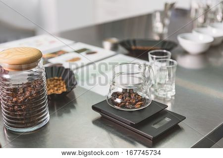 Coffee-berries are at table. Especial glass jug is on modern scales nearby other volumes with such product