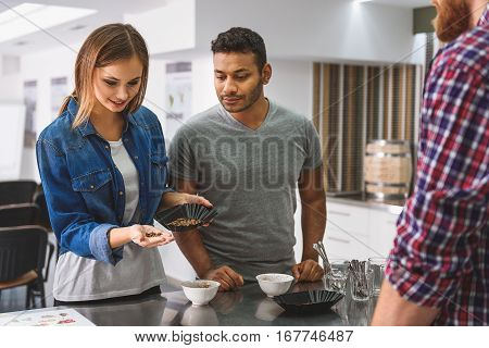 Smiling woman is standing beside man near metal table. She holding roasted coffee-berries at hand