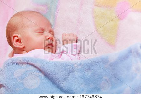 Childhood innocence concept. Little adorable newborn baby sleeping on bed with many blankets.