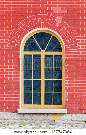 Window with arch and bars in the background of wall of red brick. From the series window of Saint-Petersburg.
