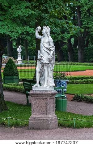 Marble sculpture on a granite pedestal in the Summer garden on a green background lattice.