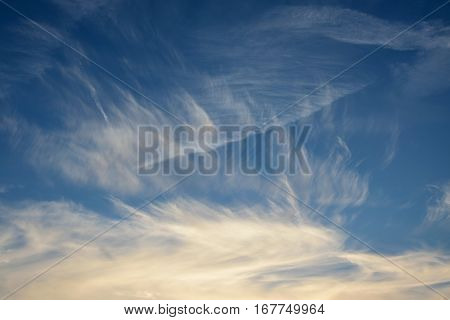 Cirrus clouds on the blue sky at sunset light.