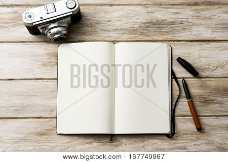 high-angle shot of an open notebook with a blank space, a pen and an old film camera on a white rustic wooden table