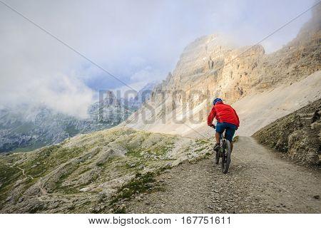 View of cyclist riding mountain bike on trail in Dolomites,Tre Cime di Laverado, South Tirol, Italy