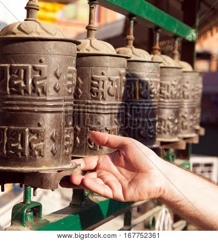 View of Prayer wheels and a hand