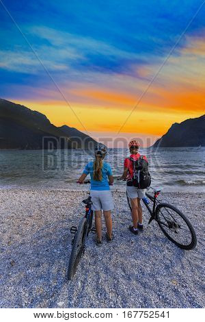 Mother and teenage daughter Family riding bikes on the beach lake.