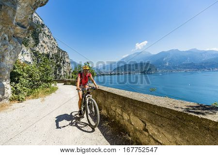Mountain biking at sunrise woman over Lake Garda on path Sentiero della Ponale, Riva del Garda, Italy