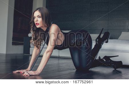 Sexy dominatrix in latex catsuit kneeling on floor indoor bdsm