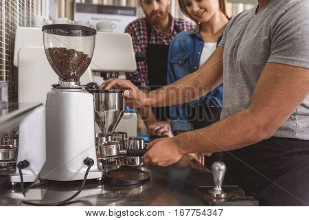 Male person is standing near special device and filling holder with roasted coffee-powder