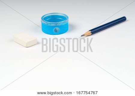 Pencil sharpener and elastic on the white paper. Back to school.