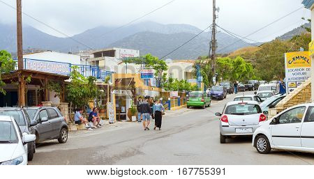 Bali Greece - April 30 2016: Modern and classic resort Greek architecture white-blue buildings stands on shore of Cretan sea. Tourists walking around city visiting sights and souvenir shops. Resort village Bali Rethymno Crete Greece