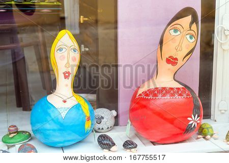 Bali Greece - April 30 2016: Author's stylised ceramic sculpture of Greek women art objects are in window of a tourist gift shop. Resort village Bali Rethymno