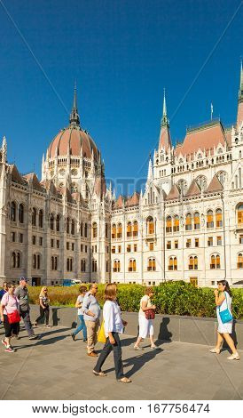 Budapest, Hungary - June 16, 2016: Group Of Tourists Passing By Hungarian Parliament Building In Bud