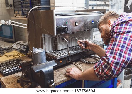 Concentrating man is inclining to apparatus and trying to renovate it. He using turn-screw