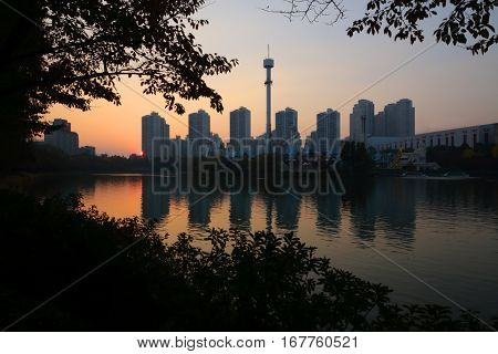Sunset, pond, highrise apartment buildings, tower in Seoul, South Korea