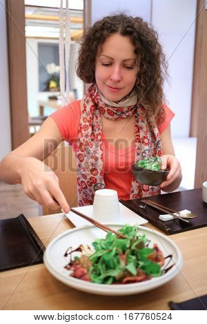 Woman taking part of salad from plate to her dish at table in cafe