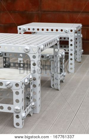 Holed chairs, benches and tables made from metal like child building kit
