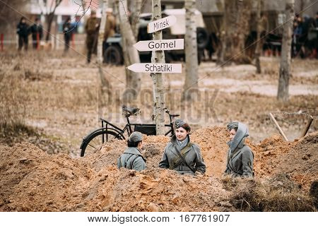 Gomel, Belarus - November 26, 2016: Three Unidentified Women Reenactors Dressed As German Wehrmacht soldiers at World War II sits in trench.