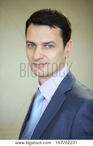 Smiling handsome brunet man in business suit with tie in studio