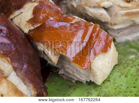 Juicy pork on the green leaf. Traditional cooked pig meat on market. Delicious juicy roasted pork. Cooked meat image for restaurant or eatery menu or recipe book. Pork meat grilled and cut for serving