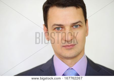Serious elegance brunet man in suit with tie next to white wall in studio