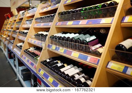 Many wine bottles are on wooden shelves at modern alcohol store
