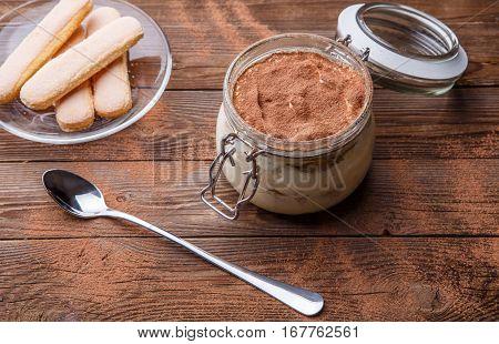 Tiramisu dessert standing on brown wooden table