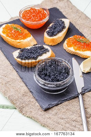 Sandwiches with red and black caviar on linen napkin on white table